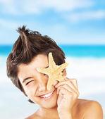 Muchacho de cara feliz con estrellas de mar en la playa — Foto de Stock