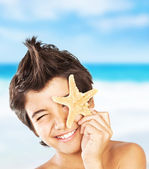 Happy face boy with starfish on the beach — Stock Photo