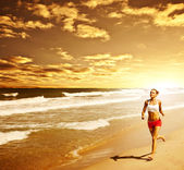 Healthy woman running on the beach — Photo