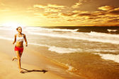Healthy woman running on the beach — Stockfoto