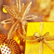 Golden Christmas gift with baubles decorations - Stock Photo