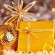 Golden Christmas gift with baubles decorations and candles — Stock Photo