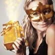 Stylish woman with golden mask and gift — Stock Photo #8016481