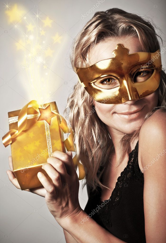 Stylish woman wearing golden mask and holding gift box, celebrating holidays, female receive gold Christmas present, new year eve party — Stock Photo #8016481