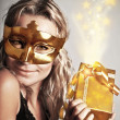 Stylish woman with golden mask and gift — Stock Photo #8055441