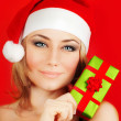 Happy Santa girl holding Christmas gift — Stock Photo
