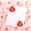 Beautiful roses with gift card & hearts — Stock Photo