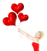 Happy girl flying, holding red heart balloons — Stock Photo