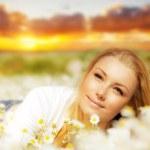 Beautiful woman enjoying flower field on sunset — Stock Photo #8987293