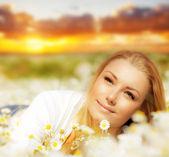 Beautiful woman enjoying flower field on sunset — Stock Photo