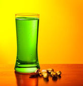 Green beer and nuts — Stock Photo