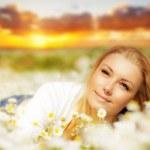 Beautiful woman enjoying flower field on sunset — Stock Photo #9068880