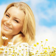 Beautiful woman enjoying daisy field and blue sky — Stock Photo #9148646