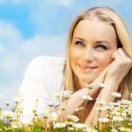 Beautiful woman enjoying daisy field and blue sky — Stock Photo