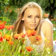 Beautiful female laying on the flower field — Stock Photo #9314864