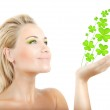 Beautiful woman holding clover leaves — Stock Photo