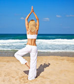 Healthy yoga exercise on the beach — Stock Photo