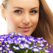 Beautiful female holding flowers — Stock Photo