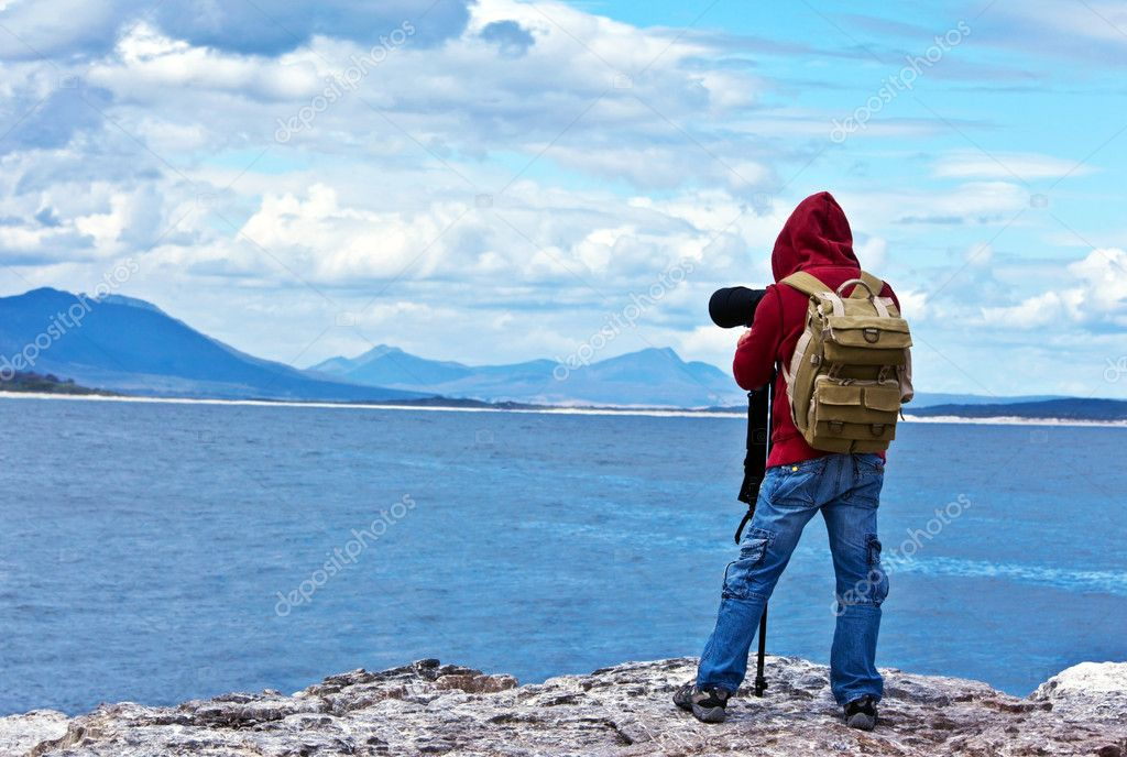 Wildlife photographer traveler enjoying ocean view from top of the mountain, backpacker hiking and taking pictures of South African landscapes, safari tour vacation, adventure and freedom concept — Stock Photo #9913661