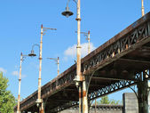 Old bridge of iron oxidized with street lamps — Stock Photo