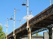 Old bridge of iron oxidized with street lamps — Stock Photo