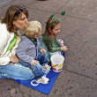 Stock Photo: Young mom with two children watching Saint Patrick's Day Parade