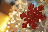 Red snowflake and Christmas lights — Stock Photo