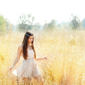 Asian indian woman walking in golden dried field — Stock Photo