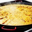 Paella rice from Valencia Spain cooking in big pan — Stock Photo