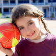 Brunette little girl football player and ball smiling — Стоковая фотография