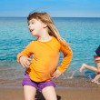 Blond kid girl dancing at the beach and friend run - Stock Photo