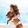 Brunette kid girl with dog on the sea — Stock Photo
