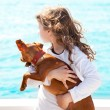Brunette kid girl with dog on the sea — Stock Photo #10583271
