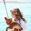 Stock Photo: Brunette kid girl with dog on the sea