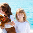 Sister kid girls with dog on the sea — Stock Photo