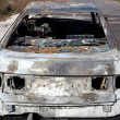 Burned out car in street - Stock Photo