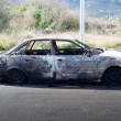 Stock Photo: Burned out car in street