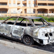 Burned out car in street - ストック写真