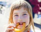 Blue eyes little girl eating churros smiling — Stock Photo