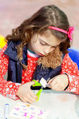 Little kid girl working at school doing workshop — Stock Photo