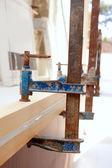 Carpenter screw clamp tool pressing wood slats — Stock Photo