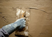 Trowel with glove hand plastering cement mortar — Stock Photo