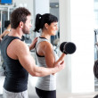 Gym woman personal trainer with weight training - Stock Photo