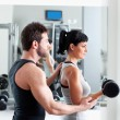 Foto Stock: Gym woman personal trainer with weight training
