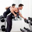 Man with weight training equipment on sport gym - Stock Photo