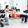 Gym personal trainer man with weight training - Stock Photo