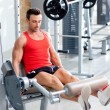 Man lifting weights with a leg press on sport gym - Stock Photo