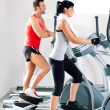 Man and woman with elliptical cross trainer at gym — Stock Photo