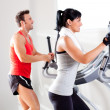 图库照片: Man and woman with elliptical cross trainer at gym
