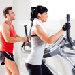 Foto Stock: Man and woman with elliptical cross trainer at gym